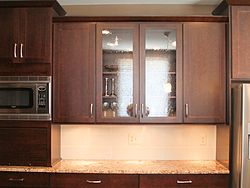 Warm Kitchen With Backsplash Details - Glass Cabinet Doors